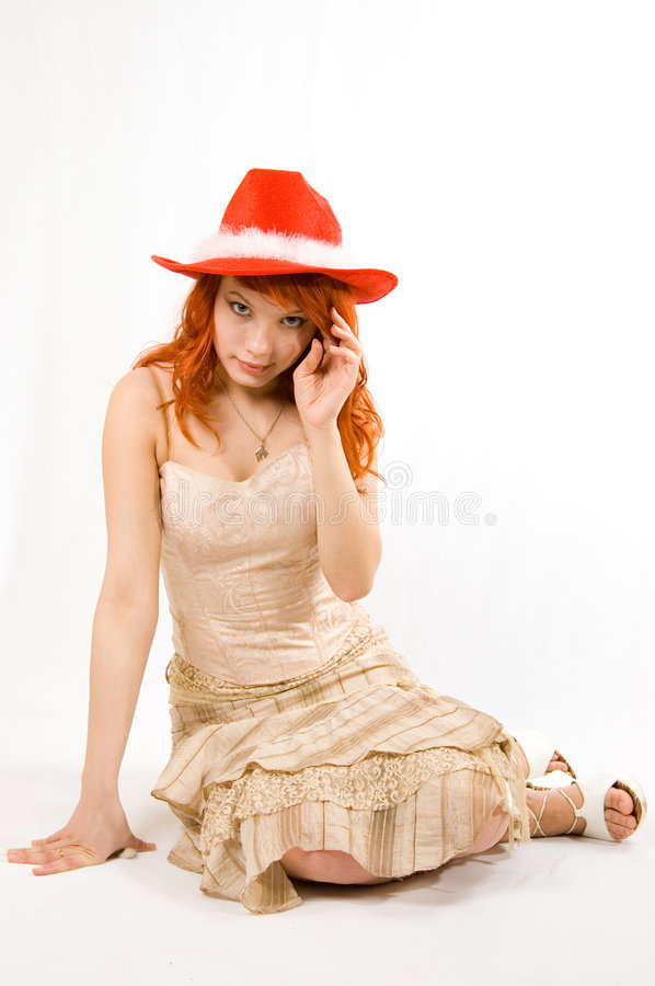 Pretty girl in a red hat. Pretty girl in a red Christmas cowboy hat sitting isolated on white royalty free stock photos