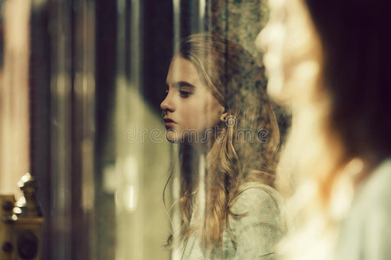 Pretty girl reflected from window glass royalty free stock photos