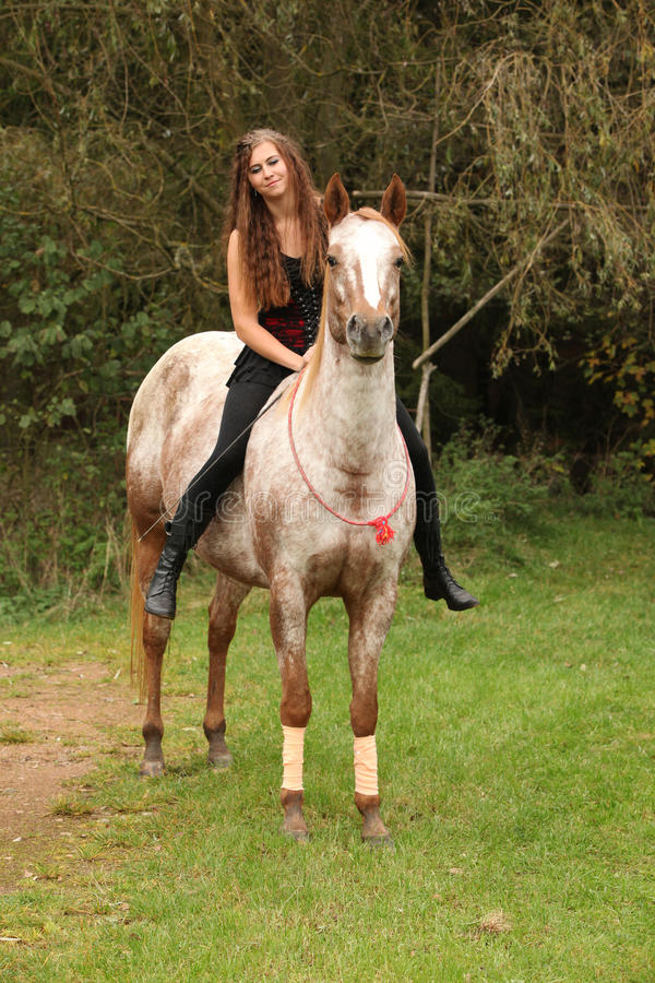 Pretty girl riding a horse without any equipment. In autumn royalty free stock image