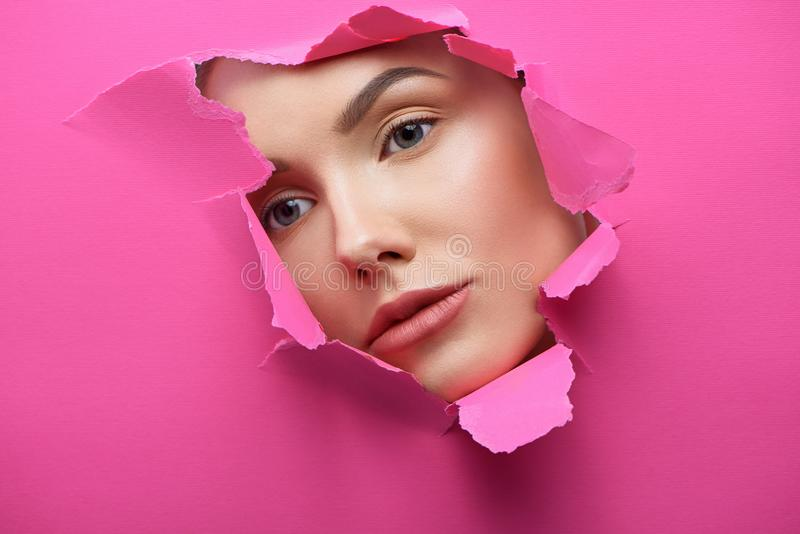 Pretty girl`s face in the hole of lacerated pink cardboard. royalty free stock photos