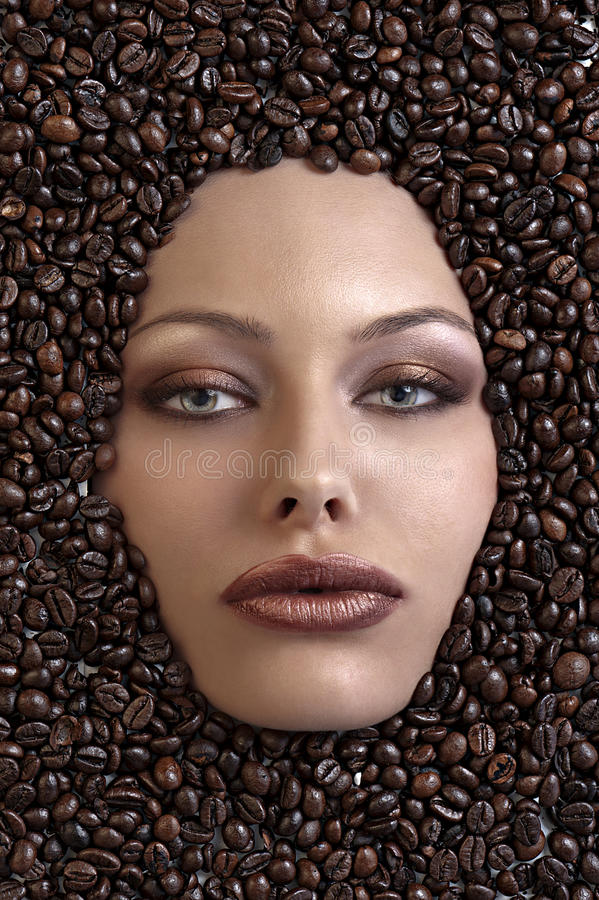 Pretty girl's face immersed in coffee beans stock photo