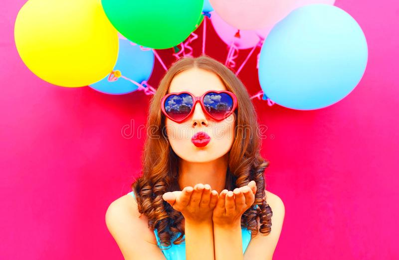 Pretty girl sends an air kiss holds an air colorful balloons. On a pink background stock image