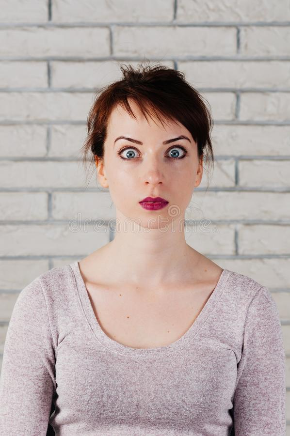 A pretty girl with shocked face, wide opened eyes. A pretty girl with surprised face, wide opened eyes, with white brick wall in the background. Face mimic stock images