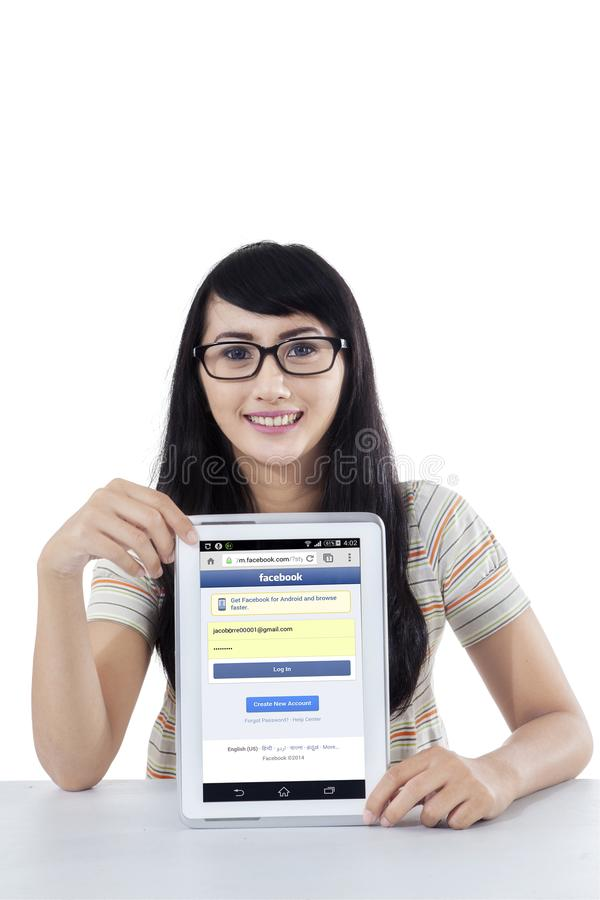 Pretty girl showing facebook profile on tablet. JAKARTA, SEPTEMBER 21, 2015: Portrait of young asian girl with glasses, showing facebook profile on the digital stock photo