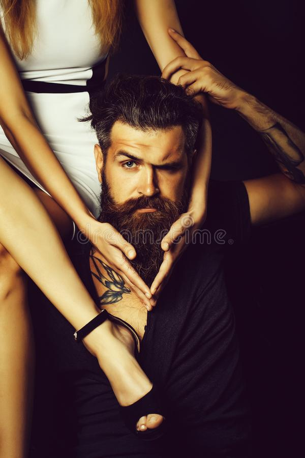Pretty girl sits on man. Pretty girl with sexy slim legs sits on shoulder of handsome man hipster graying brunette with long beard and moustache with swallow stock images