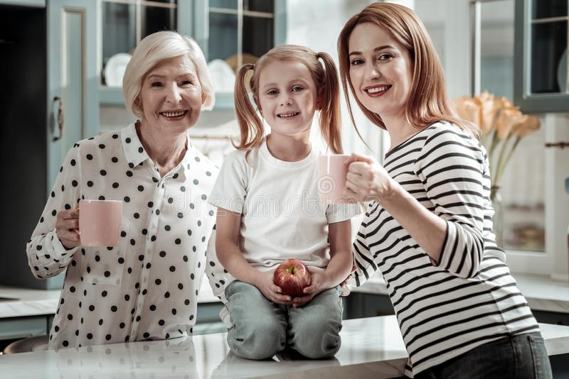 Pretty girl sitting between her mother and grandmother with apple in her hand stock photography