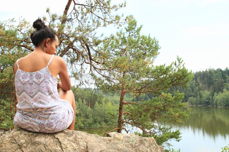 Pretty girl sitting on rock watching water royalty free stock image