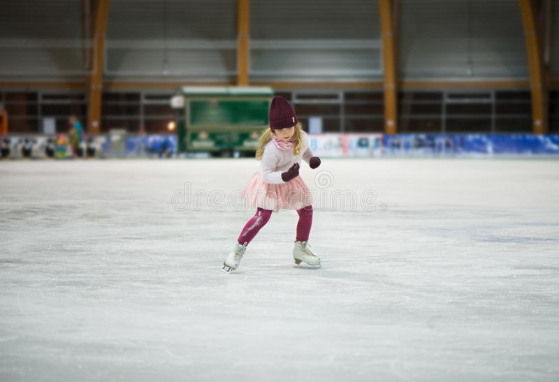Pretty girl skates in a red cap, warm gloves and sweater. Pretty little girl skates in a red cap, warm gloves and sweater royalty free stock images