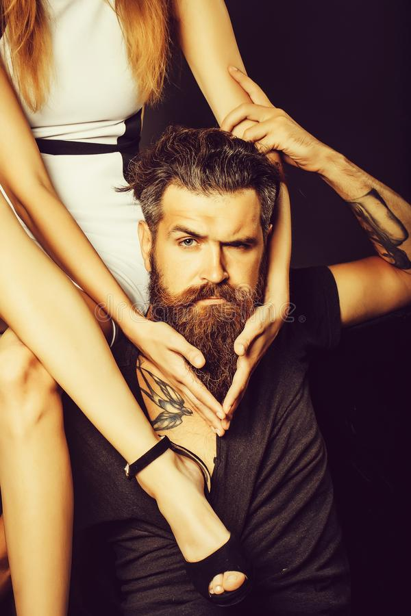 Pretty girl sits on man. Pretty girl with slim legs sits on shoulder of handsome men hipster graying brunette with long beard and moustache with swallow tattoo royalty free stock photo