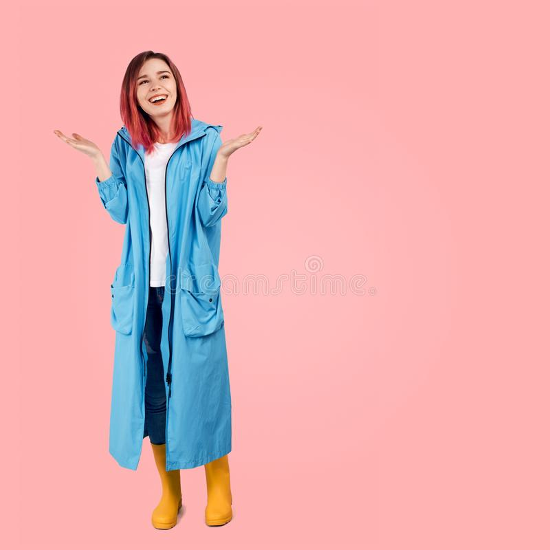 Pretty girl smiles widely and spreads her hands palms up in anticipation of beautiful weather and ended rain. She wearing a blue coat and rubber boots. Square royalty free stock image