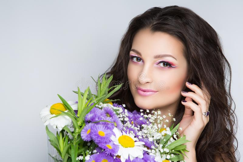 Woman with flowers. Pretty girl sniffing flowers bouquet. Creative young lady bright makeup brunette hair. Streams of flowers, shiny cheek colored big eyes pink royalty free stock photos