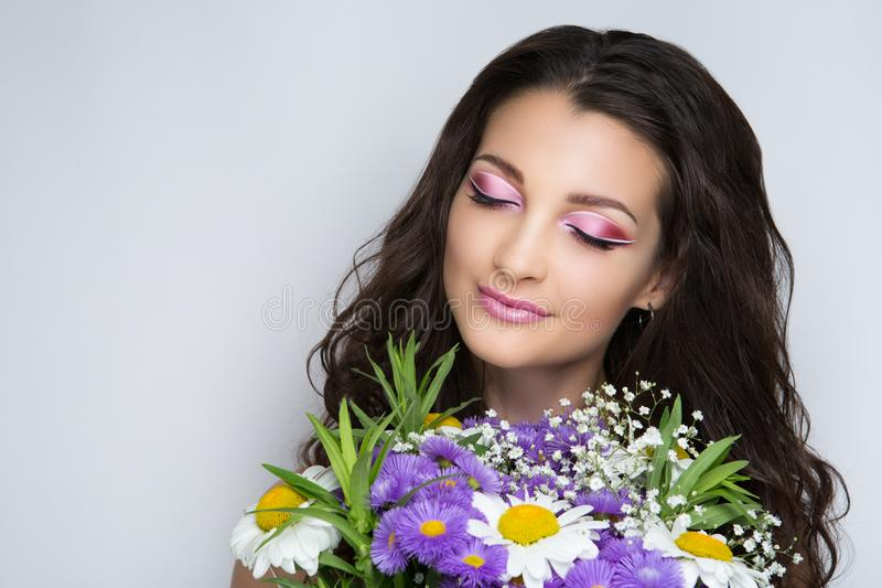 Woman with flowers. Pretty girl sniffing flowers bouquet. Creative young lady bright makeup brunette hair. Streams of flowers, shiny cheek colored big eyes pink royalty free stock image