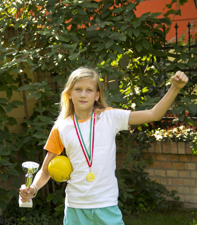 Pretty girl with sports medal and cup