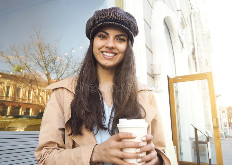 Pretty girl stand on the street with cup of coffee by the cafe wearing trench coat and cap royalty free stock photos
