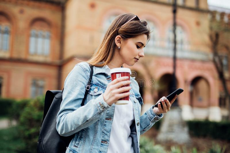 Pretty girl stand on the street typing on phone and drink coffee to go. Pretty girl stand on the street typing on phone and drink coffee stock images