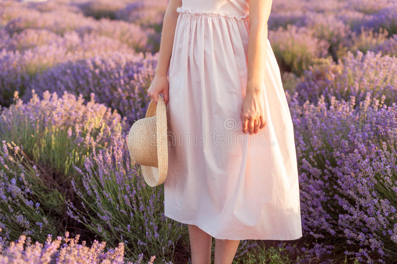 Pretty girl standing in the lavender field with fedora hat in her hand Long pink dress stock photo
