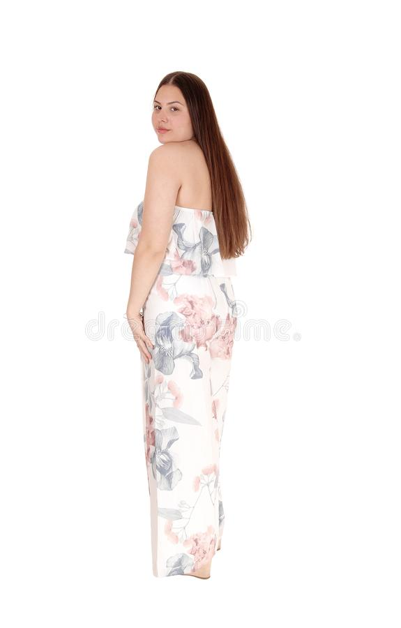 Pretty girl standing in long colorful summer dress from the back royalty free stock photo