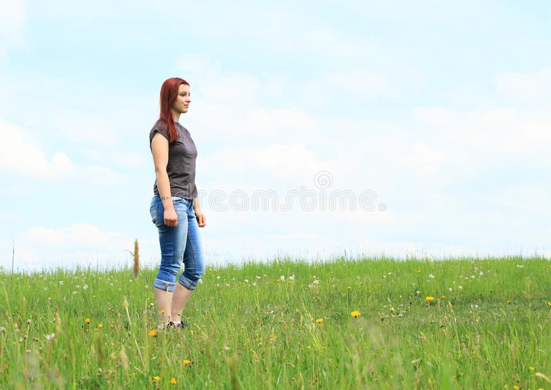 Pretty girl standing on meadow royalty free stock photo