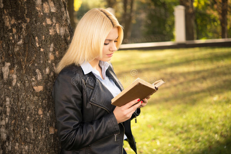 Pretty girl standing near tree and reading book stock photo