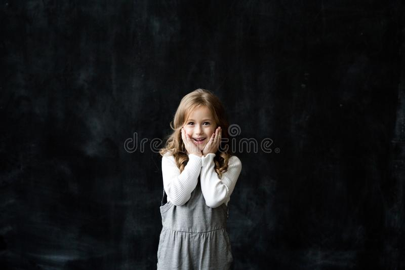 Pretty girl stands on the black background of a chalkboard and smile stock photography