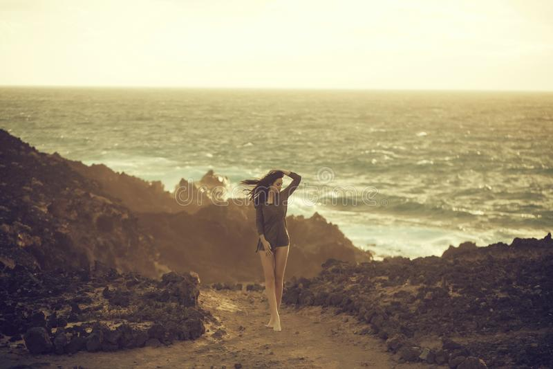 Pretty girl stands on rocky beach stock image
