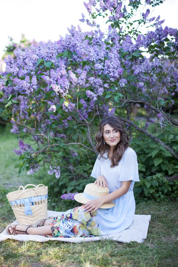 Pretty girl in a straw hat sits on a plaid and happily spends time on a picnic in the park with a lilac in the background. Concept royalty free stock image