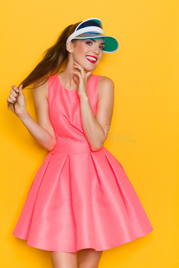 Pretty Girl In Sun Visor. Beautiful young woman in pink dress and sun visor holding her hair and posing against yellow background stock images