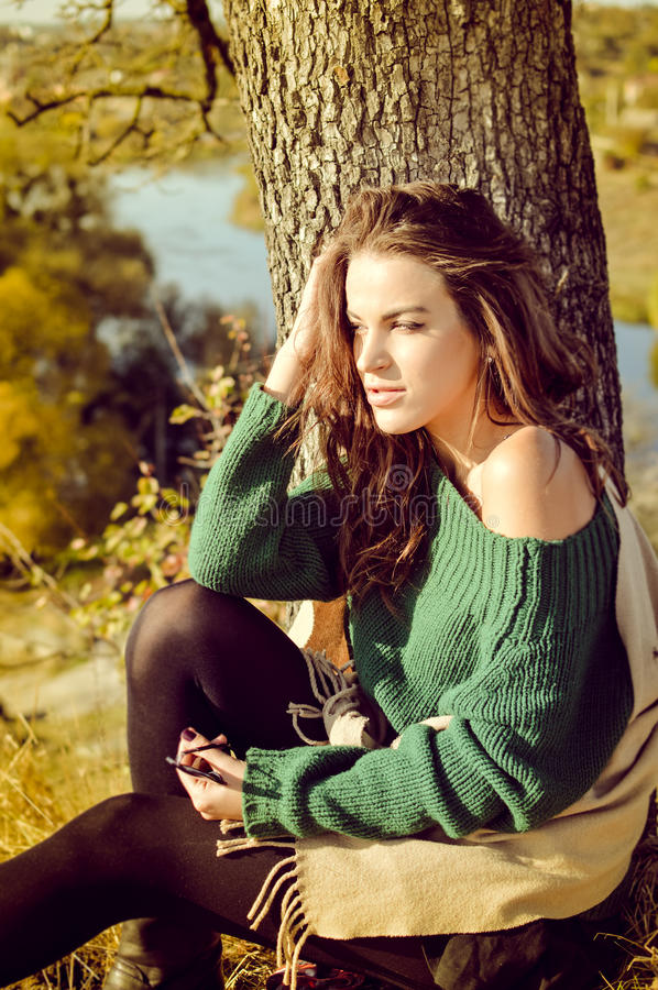 Pretty girl in sweater sunning under tree on. Picture of romantic beautiful young woman in beige shawl looking aside in sunny autumn day. Pretty girl sunning stock images