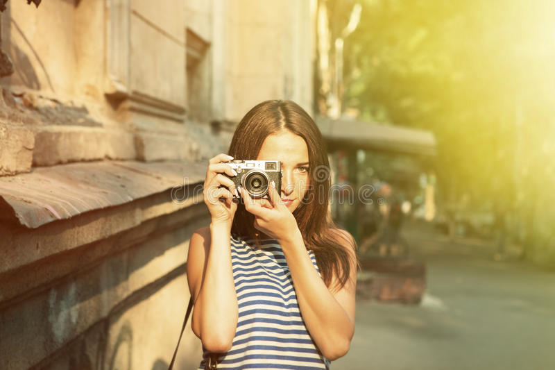 Pretty girl taking photo on the old street. Pretty girl taking photo on the street royalty free stock images
