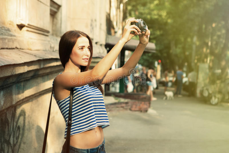 Pretty girl taking photo on the old street. Pretty girl taking photo on the street stock image