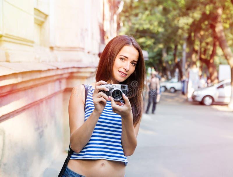 Pretty girl taking photo on the old street. Pretty girl taking photo on the street royalty free stock photos