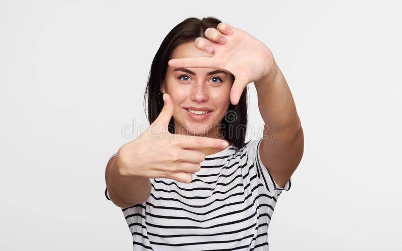Pretty girl taking picture with imaginary camera stock images