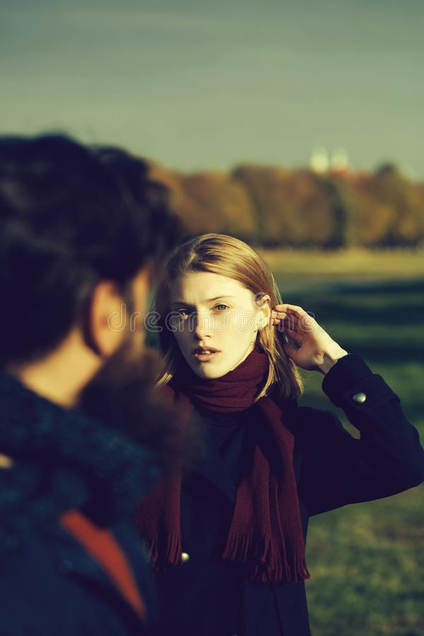 Pretty girl talks to man. Pretty girl young beautiful women with red hair and scarf talks to bearded men hipster outdoors in park on autumn day on natural royalty free stock photo