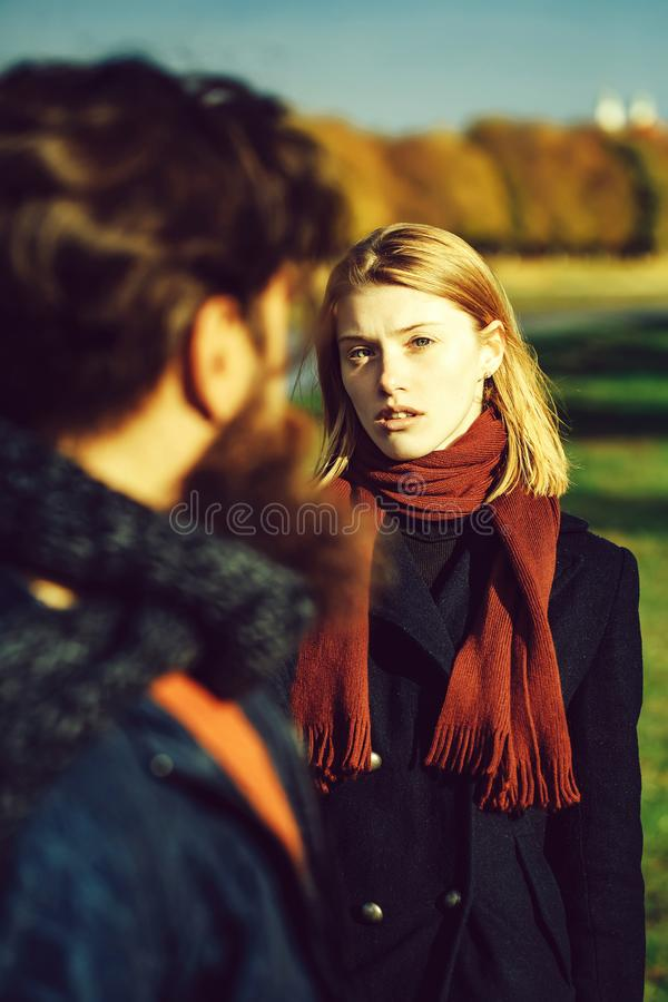 Pretty girl talks to man. Pretty girl young beautiful women with red hair and scarf talks to bearded men hipster outdoors in park on autumn day on natural stock photos