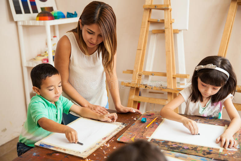 Pretty girl teaching art class. Cute female art teacher helping her students draw at an art school royalty free stock images