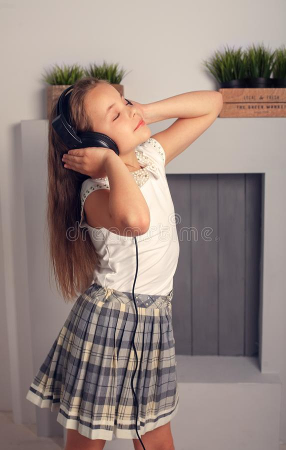 Pretty Girl teenager listening to music in headphones. The concept of lifestyle. royalty free stock photo