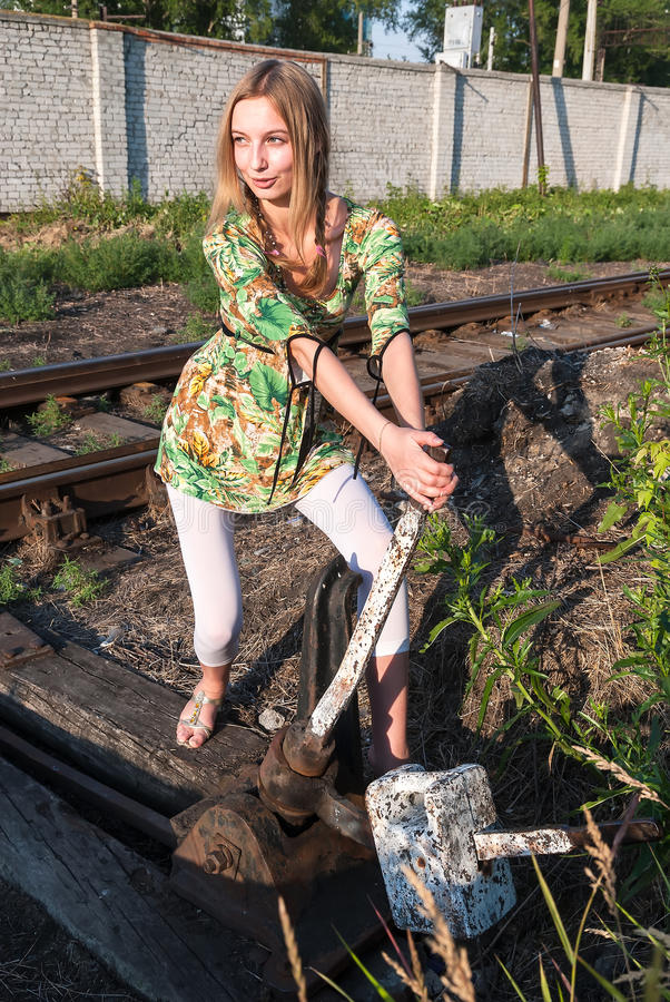 Pretty girl throws railway switch stock photos