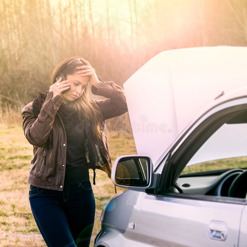 Pretty girl in trouble with broken car royalty free stock images