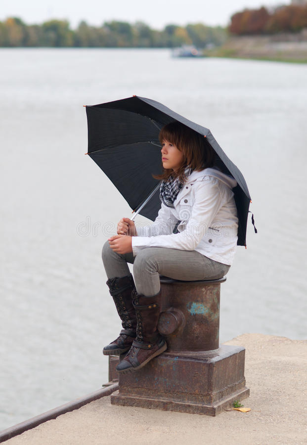 Download Pretty Girl With Umbrella Sitting On The Dock Stock Image - Image: 23851033