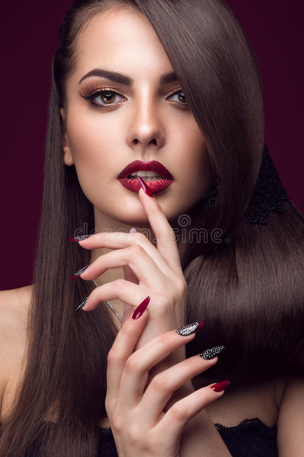 Pretty girl with unusual hairstyle, bright makeup, red lips and manicure design. Beauty face. Art nails. Studio portrait royalty free stock images