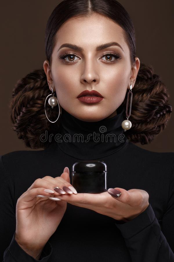 Pretty girl, unusual hairstyle, bright makeup, red lips and manicure design with a jar of nail polish in her hands stock images