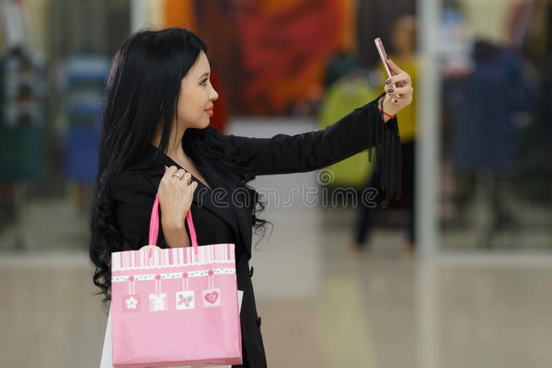 Pretty girl using her smartphone to take a selfie photo. Woman with shoppping bags in mall. royalty free stock photos