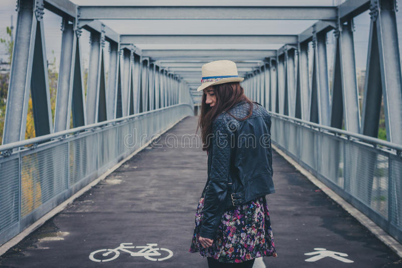 Pretty girl walking away on a bridge royalty free stock photos