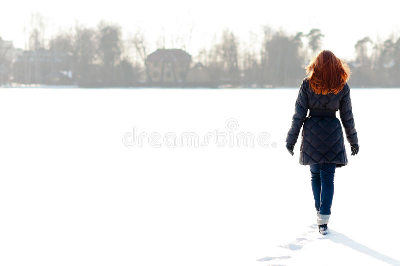 Pretty girl walking on frozen lake. Pretty red haired girl walking on frozen lake and making footpath stock image