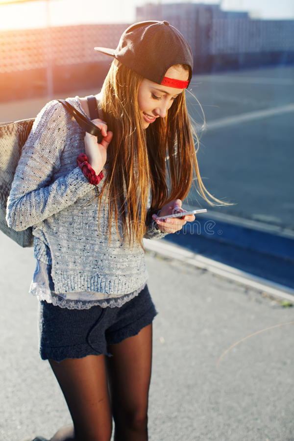 Pretty girl walking outdoors in the street while using busy a smart phone. Gorgeous young woman wearing casual spring clothes walking down a city street while stock images