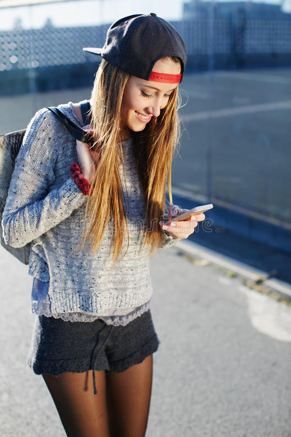 Pretty girl walking outdoors in the street while using busy a smart phone. Gorgeous young woman wearing casual spring clothes walking down a city street while stock photos