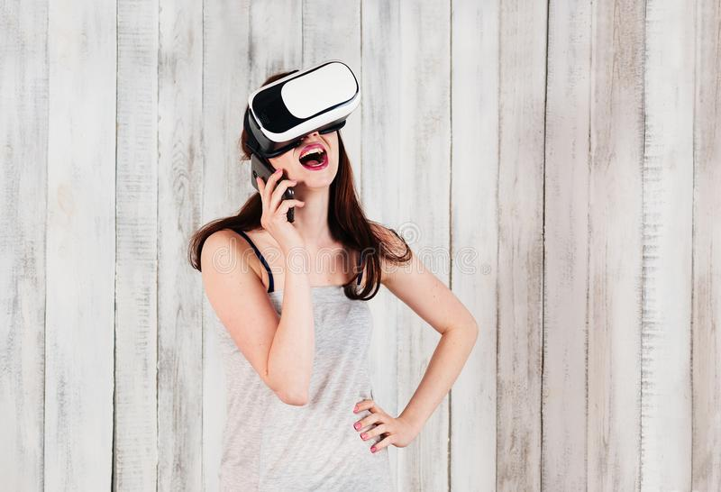 A pretty girl wearing VR glasses, laughingly talking by cellphone, white wooden background royalty free stock photo