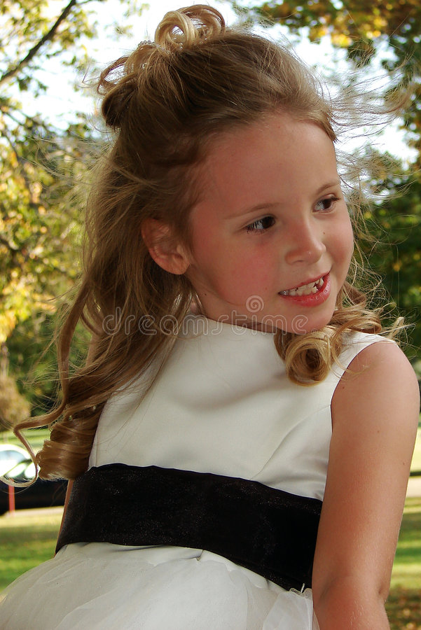 Pretty Girl In A White Dress. A pretty little girl with a nice smile in a white dress royalty free stock image