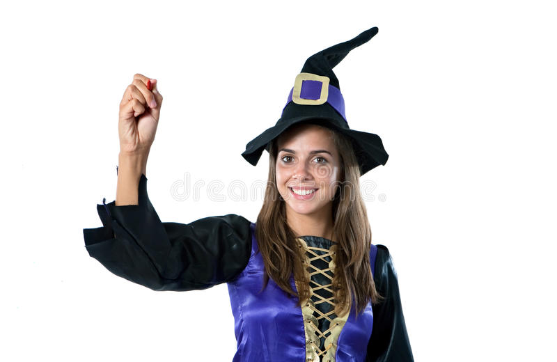 Pretty girl with witch costume writing. Isolated on white royalty free stock photo
