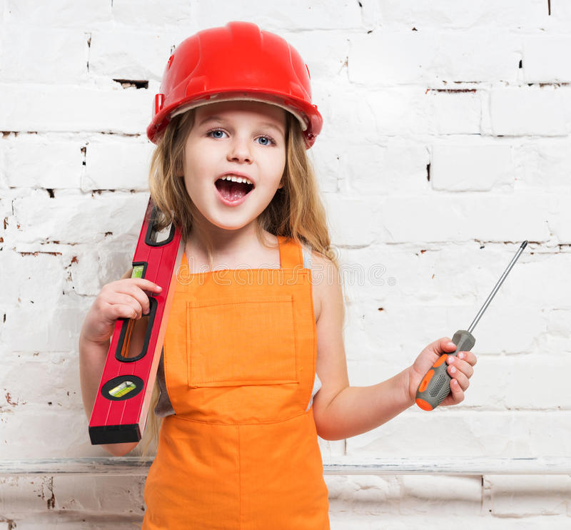 Pretty girl-worker with builing level and screwdriver stock photos
